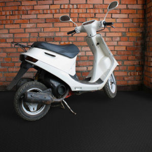 White scooter in corner wall